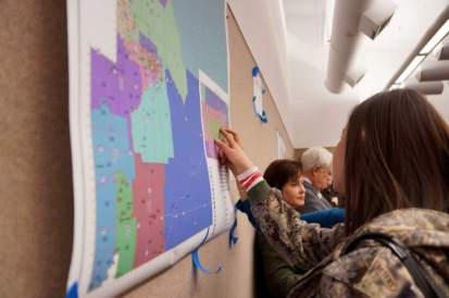 Women who attended the Weld County Republican Party biannual organizational committee meeting point to districts on a map of redrawn party districts in the county. The new districts lines were approved at the meeting on Saturday with little contention. Alison Noon, The Greeley Tribune